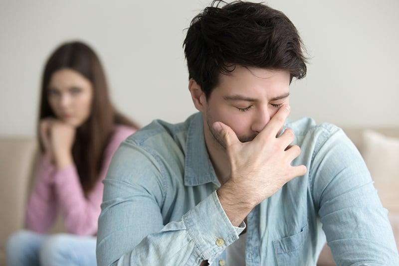 Ein verärgerter depressiver Mann, der den Mund mit der Handfläche bedeckt, während er vor seiner Freundin sitzt
