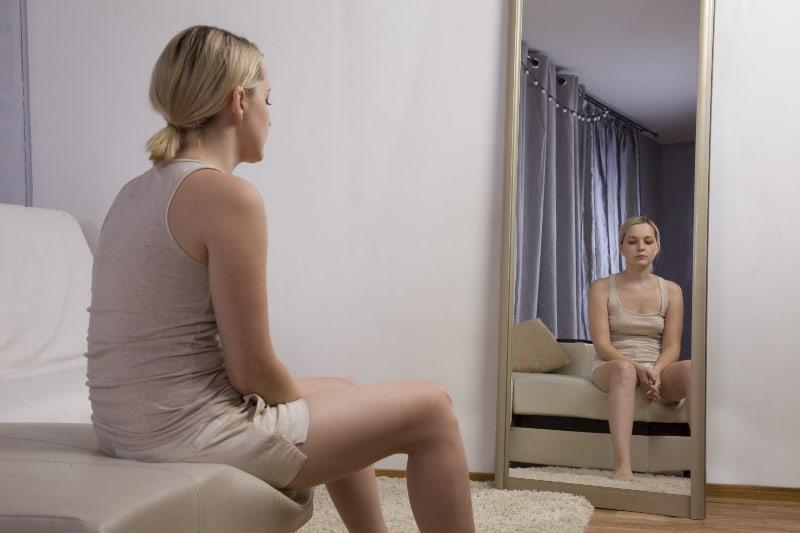 ein verärgertes Mädchen, das vor einem Spiegel sitzt