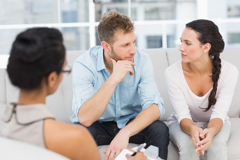 Ein Ehepaar spricht miteinander, während es vor dem Therapeuten sitzt