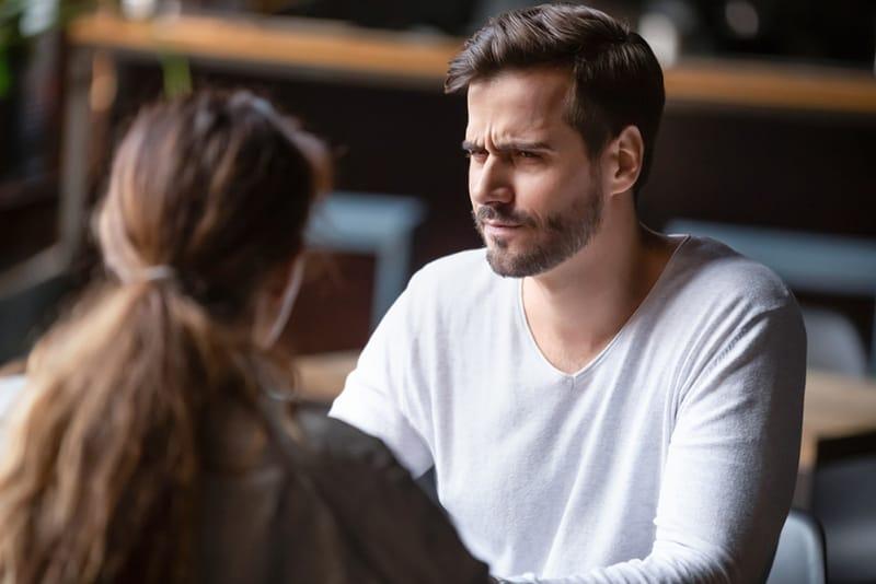 Ein verwirrter Mann, der eine Frau ansieht, während er zusammen am Tisch sitzt