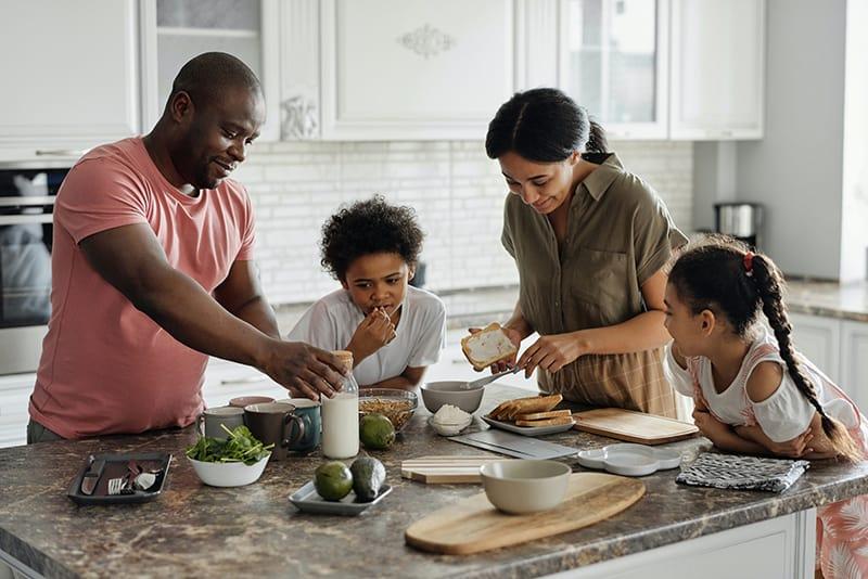 Eine Familie, die gemeinsam in der Küche zu Hause das Frühstück zubereitet