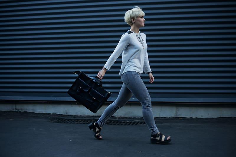 eine Frau, die auf der Straße geht und eine Handtasche hält