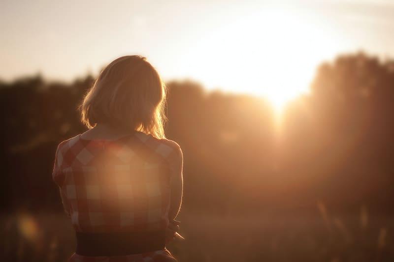 eine Frau, die einen Sonnenaufgang beobachtet, während sie alleine steht