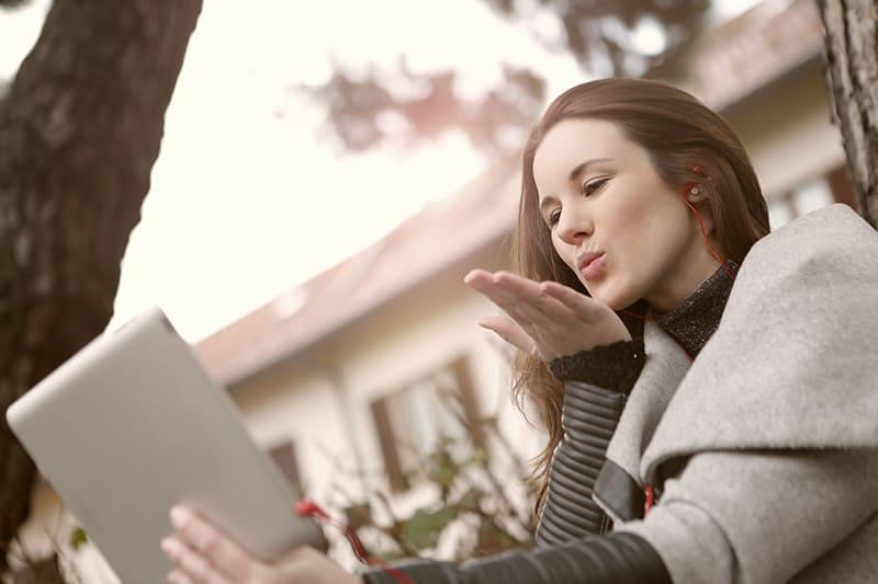 eine Frau, die während eines Videoanrufs Küsse sendet