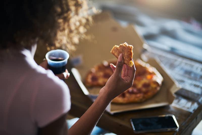 eine Frau, die Pizza isst und Cola trinkt, während sie zu Hause vor dem Fernseher sitzt