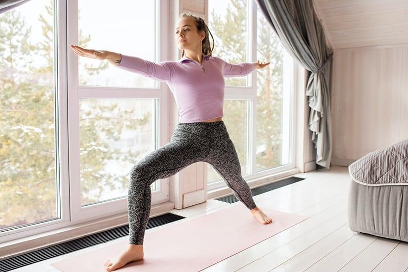 eine Frau, die Yoga im Schlafzimmer in der Nähe des Fensters macht