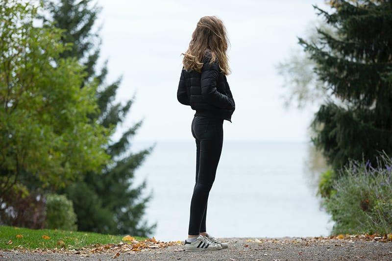 eine Frau, die alleine auf der Straße steht und überlegt, in welche Richtung sie gehen soll