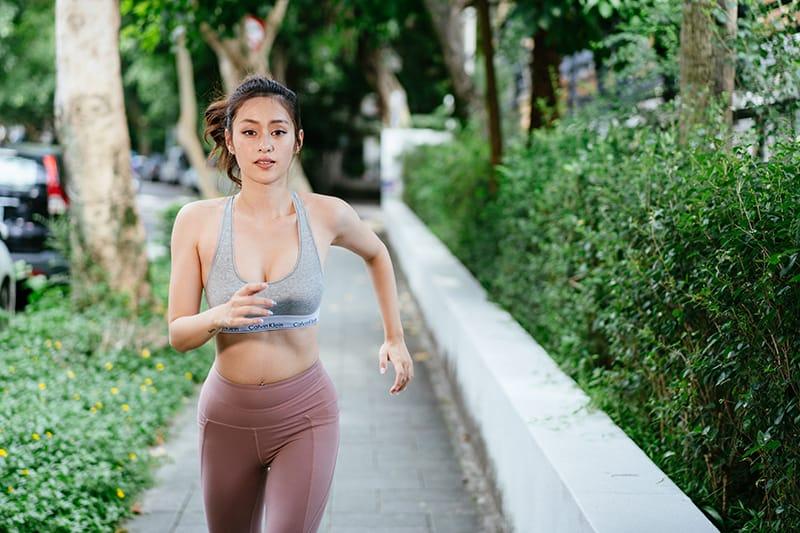 eine Frau, die tagsüber auf dem Bürgersteig joggt