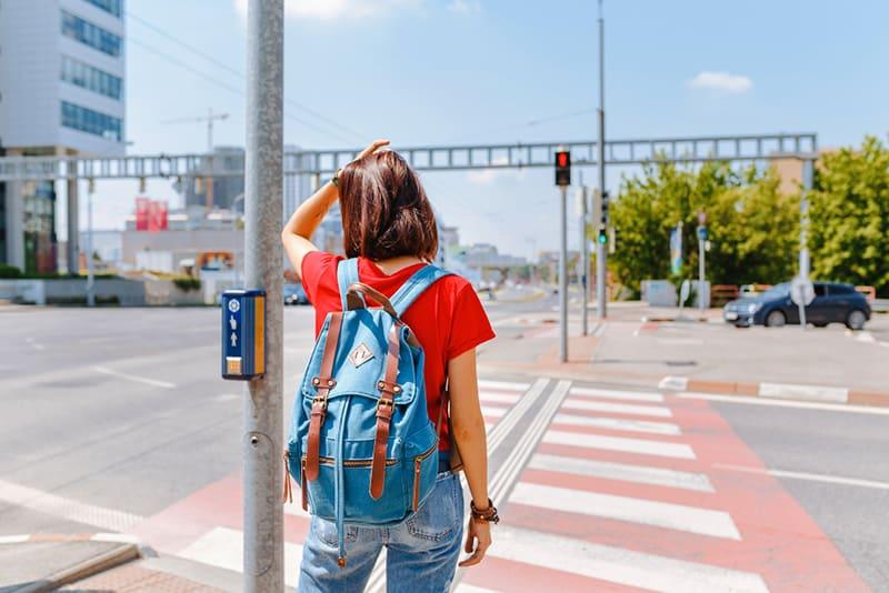 eine Frau, die auf dem Zebrastreifen steht und auf grünes Licht wartet