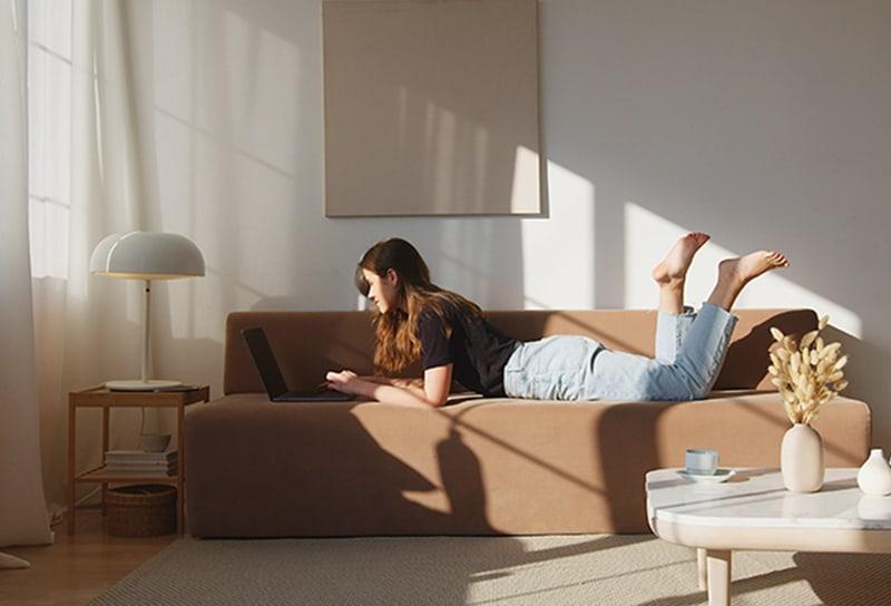 eine Frau, die auf der Couch liegt und einen Laptop benutzt, während sie sich in ihrer Wohnung entspannt