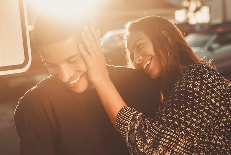 eine Frau, die das Gesicht ihres Freundes berührt, während sie zusammen lacht