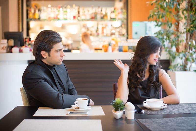 eine Frau, die den Kopf von einem Mann abwendet, während sie im Café streitet