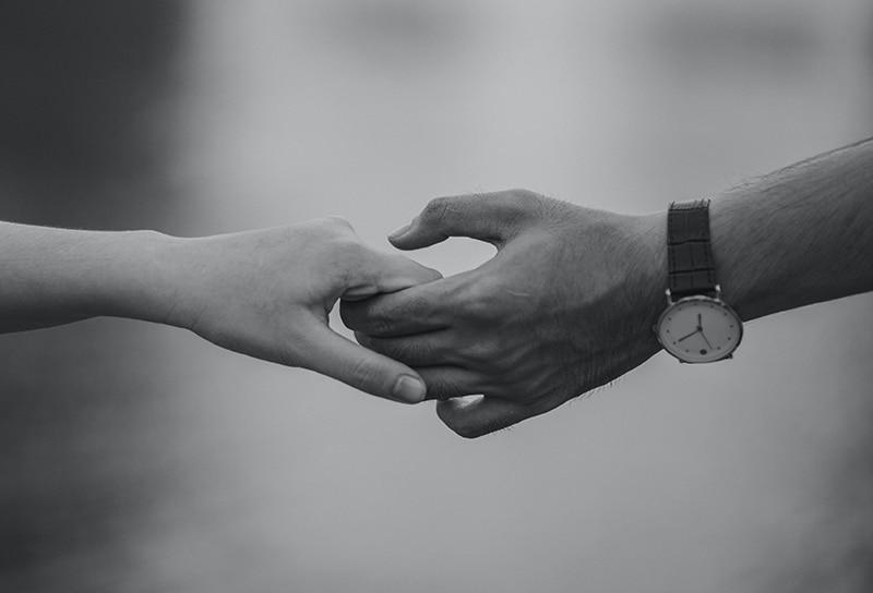 eine Frau, die die Hand eines Mannes mit einer Armbanduhr darauf hält