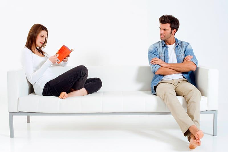 eine Frau, die ein Buch liest, und ihr verärgerter Freund, der sie ansieht, während er getrennt auf der Couch sitzt