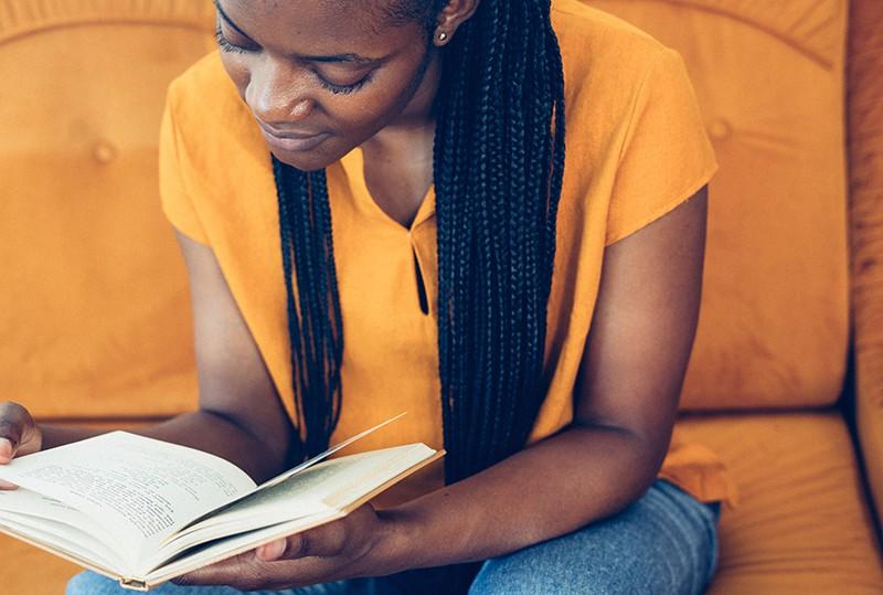 eine Frau, die ein Buch liest, während sie auf dem Sofa sitzt