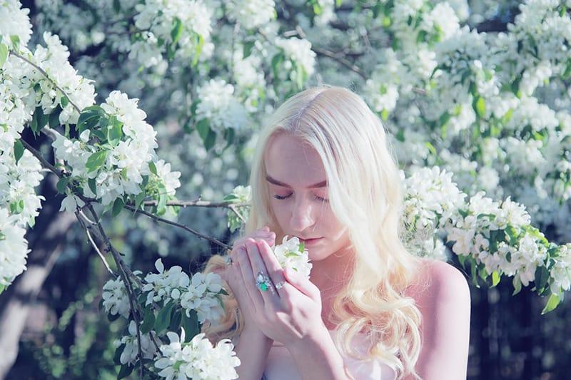eine Frau, die mit geschlossenen Augen eine Frühlingsblüte riecht