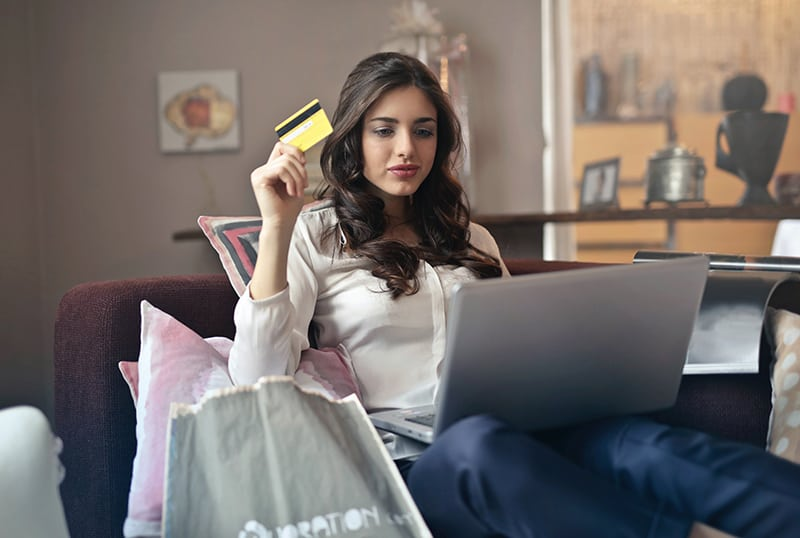 eine Frau, die eine Kreditkarte hält, während sie auf der Couch sitzt und online mit einem Laptop einkauft