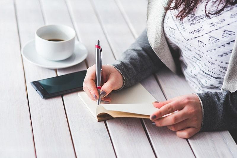 eine Frau, die eine To-Do-Liste schreibt, während sie am Tisch sitzt
