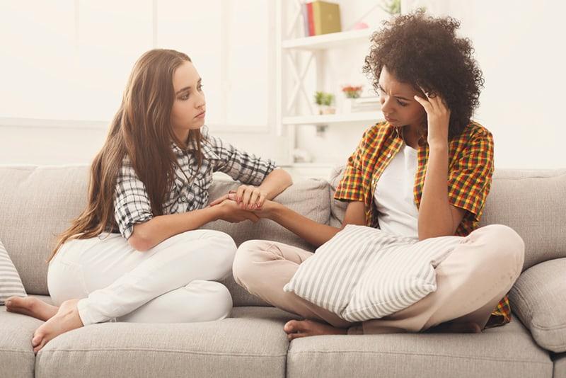 eine Frau, die eine weinende Freundin tröstet, während sie auf der Couch sitzt