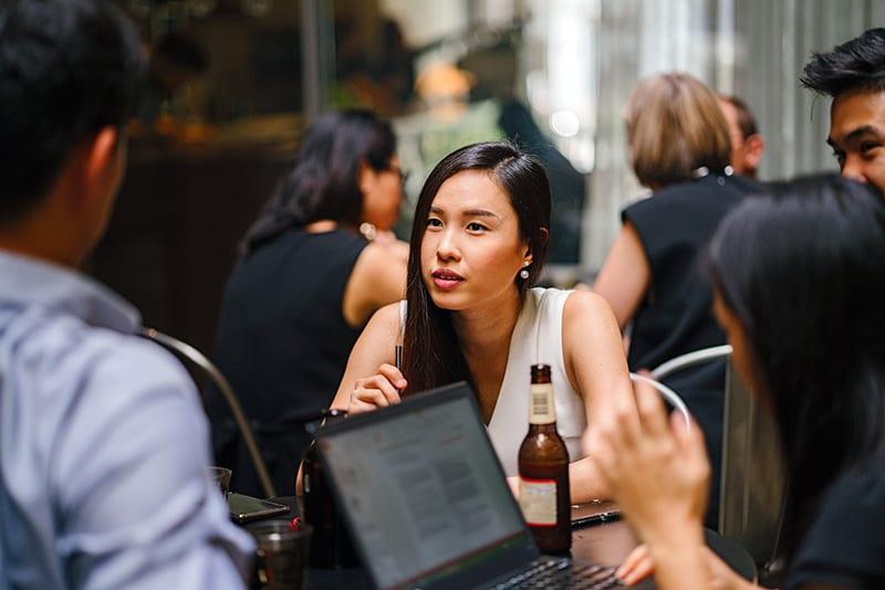 eine Frau, die einem Mann zuhört, während sie mit Freunden im Café sitzt