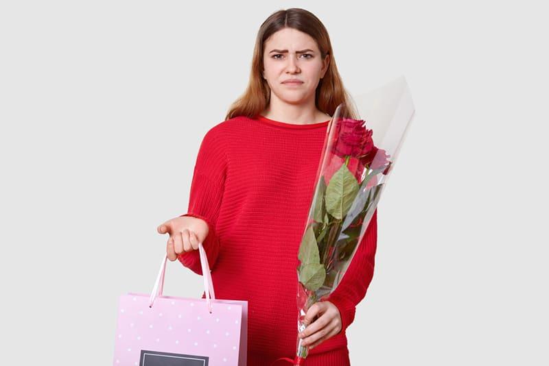 eine Frau mit einem Blumenstrauß und einer Geschenktüte, die unbefriedigt aussieht