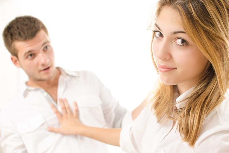 Eine Frau drückt einen Mann, der versucht, mit ihr zu sprechen