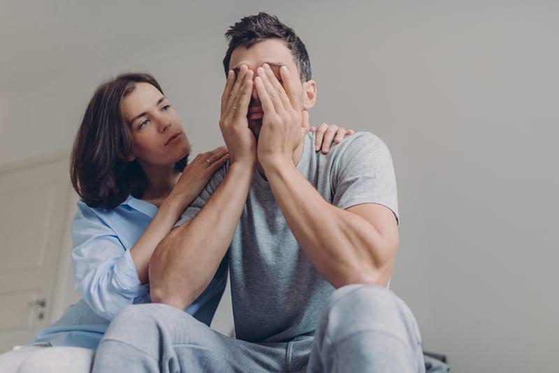 eine Frau, die einen depressiven Ehemann tröstet, während sie auf dem Bett sitzt
