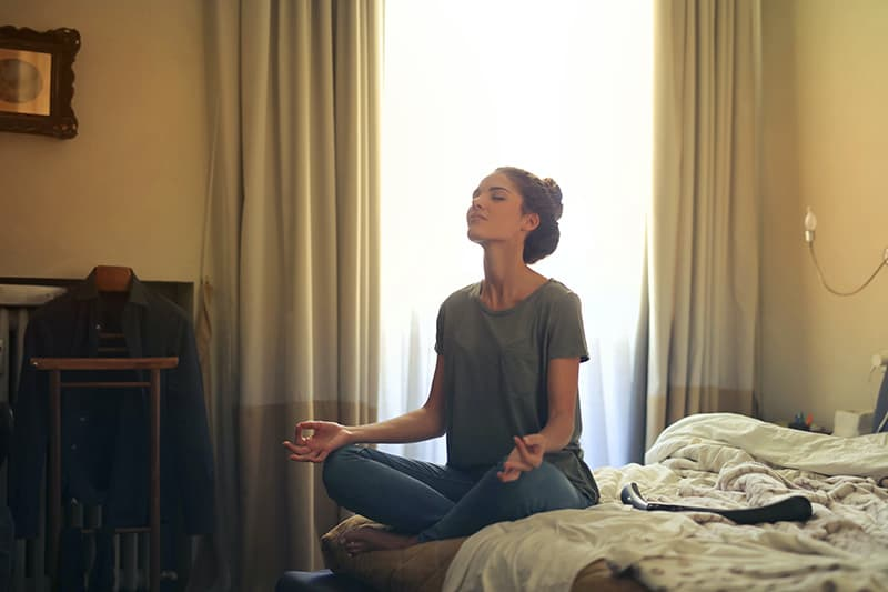 eine Frau, die im Schlafzimmer meditiert, während sie auf dem Bett sitzt