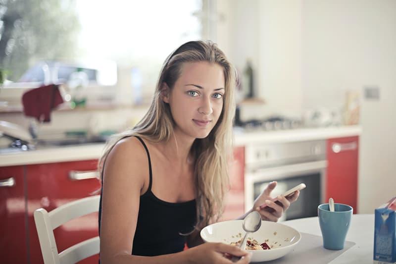 eine Frau, die Frühstück in der Küche isst und Smartphone hält