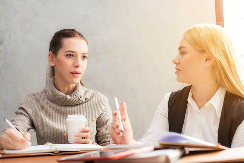 eine Frau, die in ein Notizbuch schreibt, während sie einem Kommunikationstrainer am Schreibtisch aufmerksam zuhört
