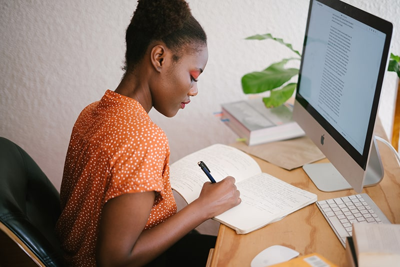 eine Frau, die in ein Notizbuch schreibt, während sie im Büro vor einem Computer sitzt