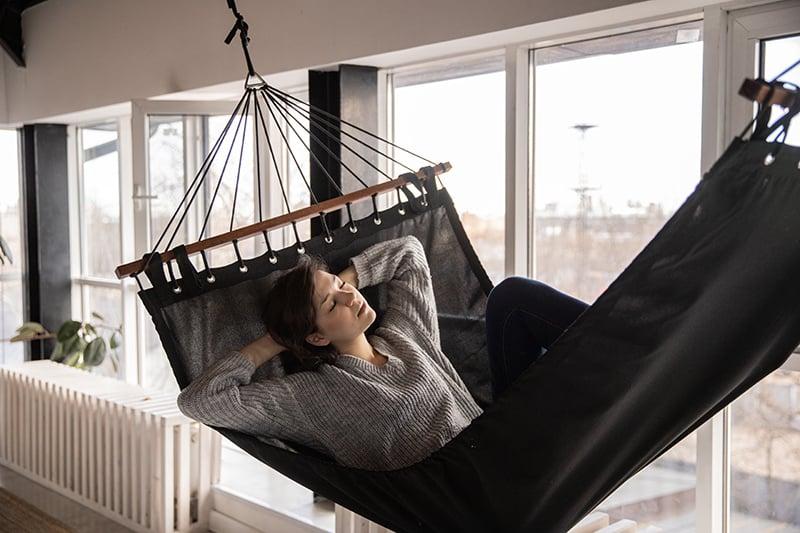 eine Frau, die in einer Hängematte im Haus schläft