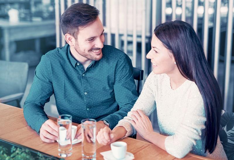 eine Frau, die mit einem Mann spricht, während sie zusammen an der Theke sitzt