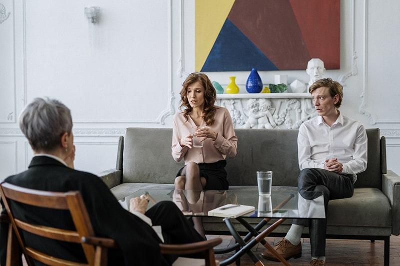 eine Frau, die mit einem Therapeuten spricht, während sie neben ihrem Ehemann auf der Couch sitzt