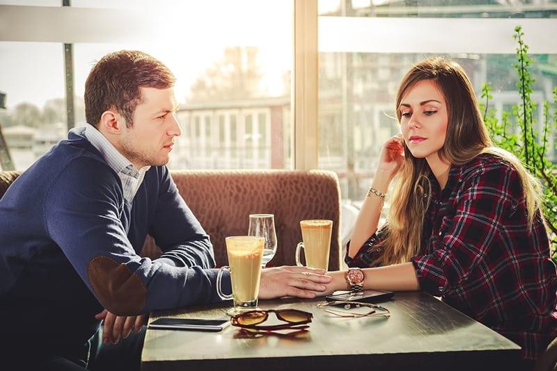 eine Frau, die nach unten schaut, während ihr Freund ihre Hand hält, während er zusammen im Café sitzt