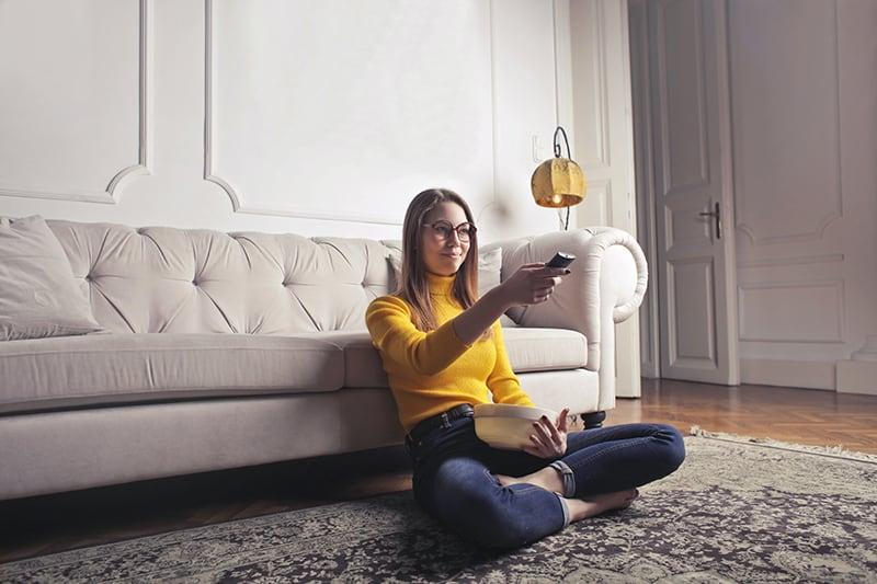 eine Frau, die zu Hause entspannt und fernsieht