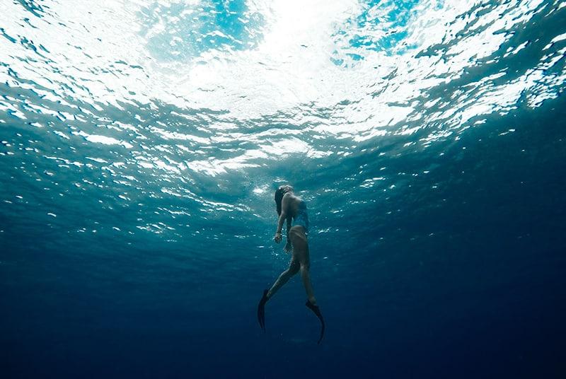 eine Frau, die unter Wasser mit Schwimmflossen schwimmt