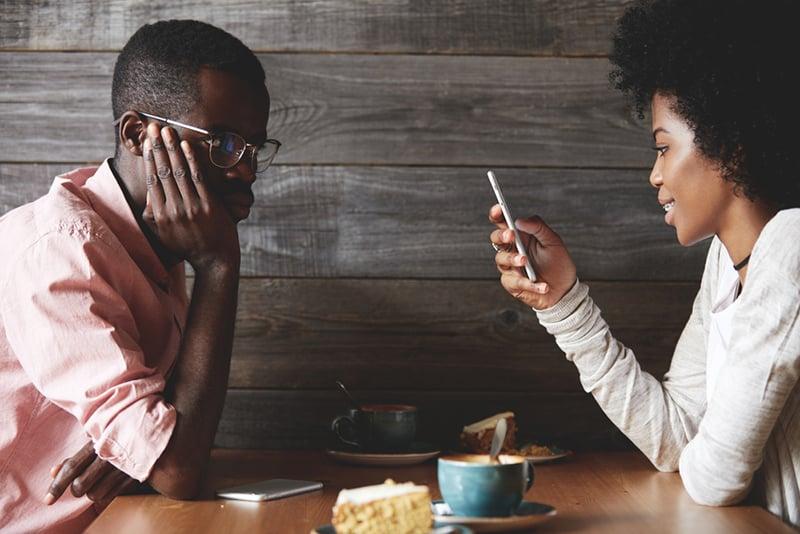 eine Frau, die während eines Dates ein Telefon benutzt und sich beleidigt fühlt
