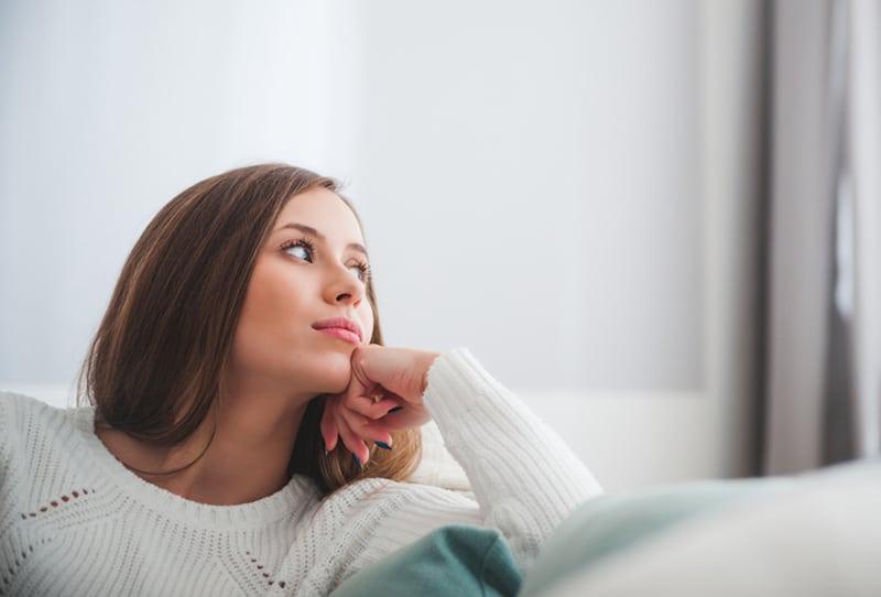 Eine Frau sitzt zu Hause auf dem Sofa und denkt tief über etwas Wichtiges nach