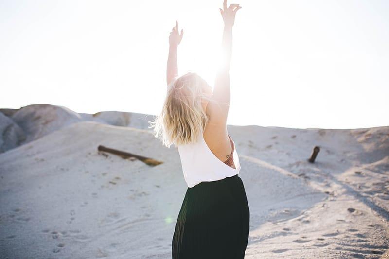 Eine Frau hebt ihre Hände und steht tagsüber im Sand