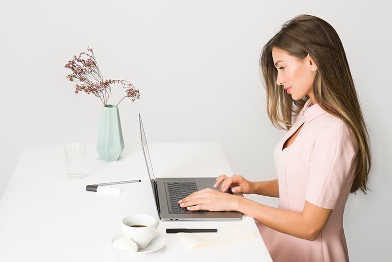 eine Frau in einem rosa Kleid mit einem Laptop im Büro
