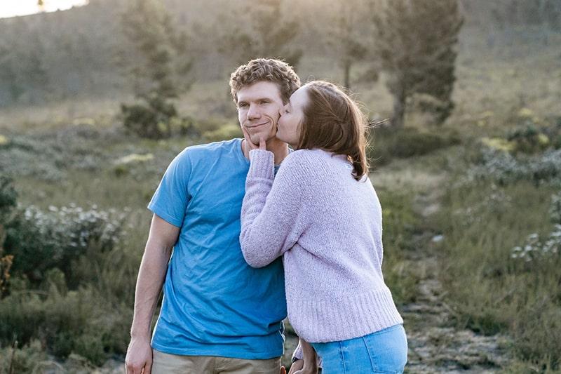 Eine Frau küsst ihren Freund auf die Wange, während sie auf dem Feld steht
