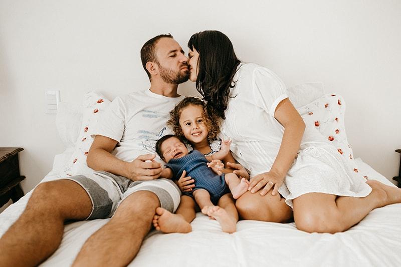 eine Frau küsst ihren Mann auf die Wange, während ihre Kinder zwischen ihnen auf dem Bett sitzen