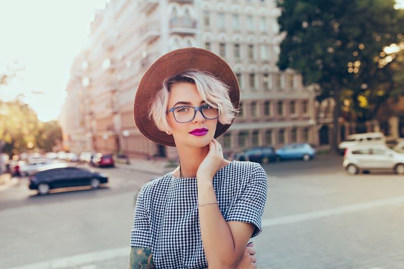 eine Frau mit Hut, der den Hals mit der Hand berührt, während sie auf dem Bürgersteig steht