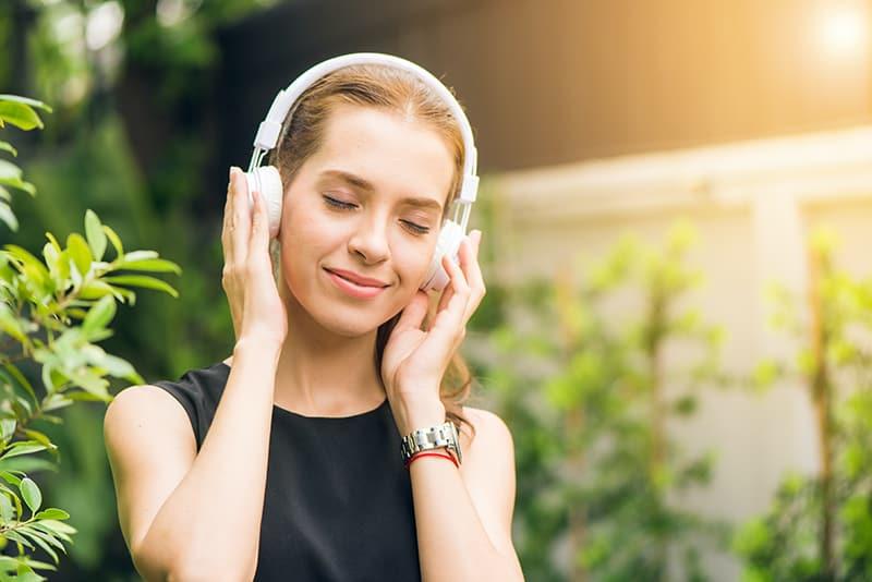 eine Frau mit Kopfhörern, die Musik hört, während sie draußen steht