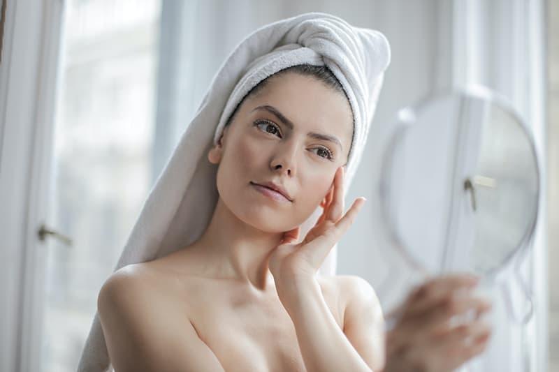 eine Frau mit einem Handtuch auf dem Kopf, die sich in den Spiegel schaut