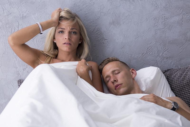 eine Frau mit einem Kater, die neben einem schlafenden Mann in einem Bett liegt