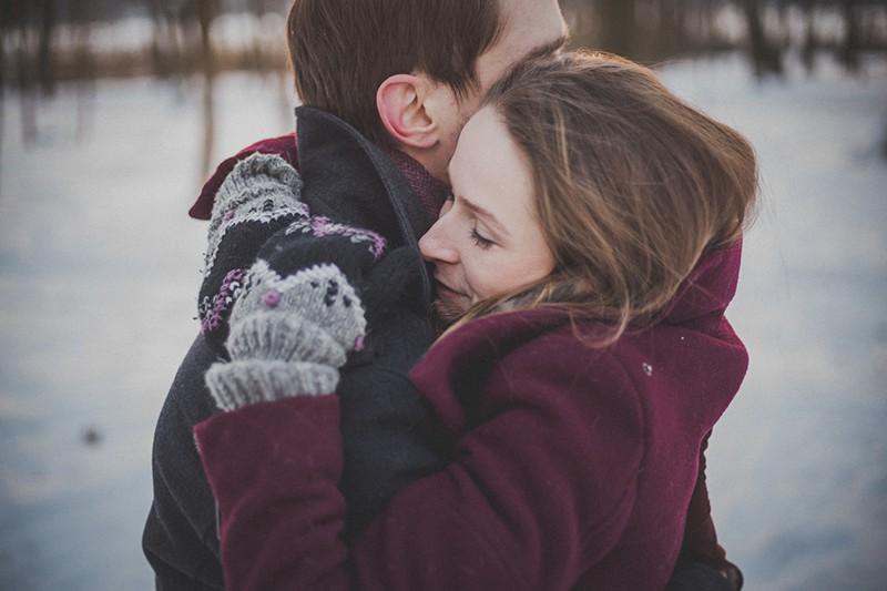 eine Frau mit geschlossenen Augen umarmt einen Mann im Schnee