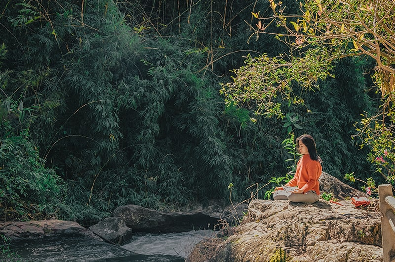 eine Frau, die auf dem Stein sitzt und in der Natur meditiert