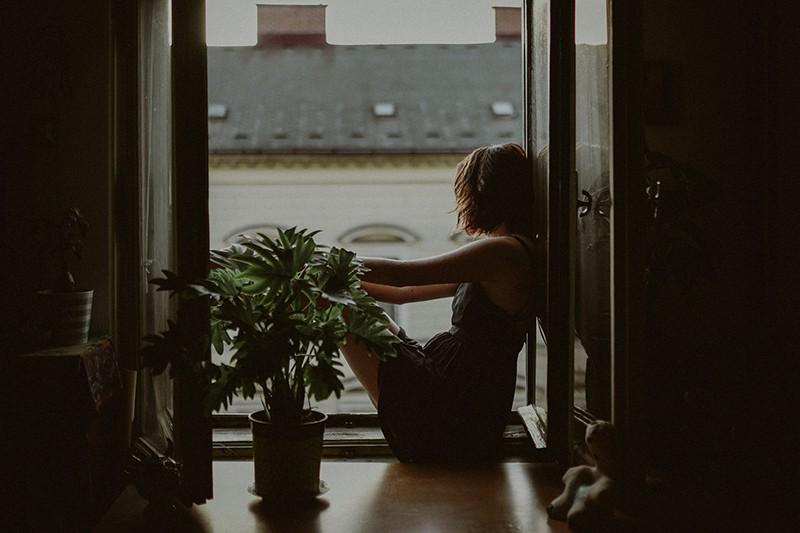 eine Frau, die auf dem Fensterbrett sitzt und nach draußen schaut